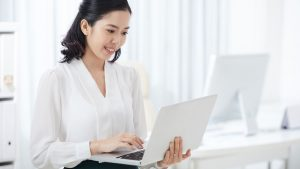 Standing woman in white blouse types on white laptop in an office of white furniture in Singapore