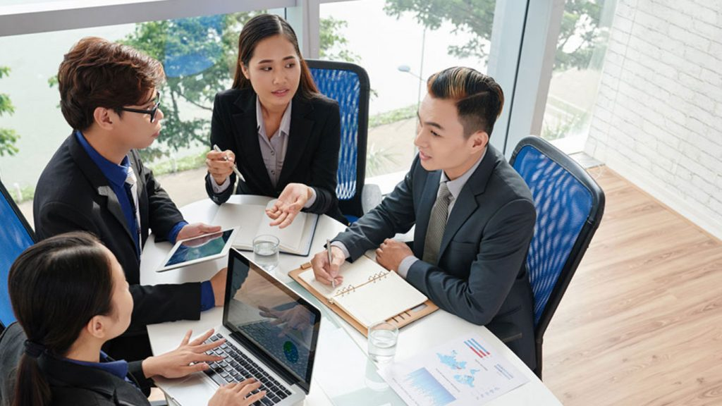 2 men and 2 women in discussion inside an office in Singapore