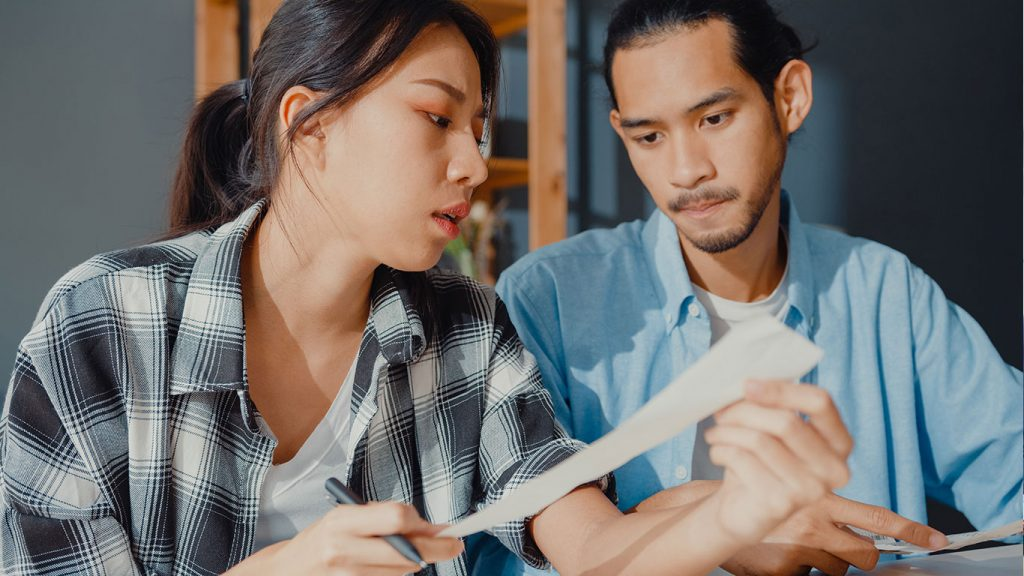 A normal income couple discuss their budget before applying for a loan in Singapore