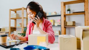 Young female start-up business owner on the phone using stylus tablet with packages on table in Singapore