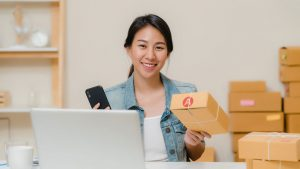 Young female small business owner smiling holding a package and phone behind laptop in Singapore