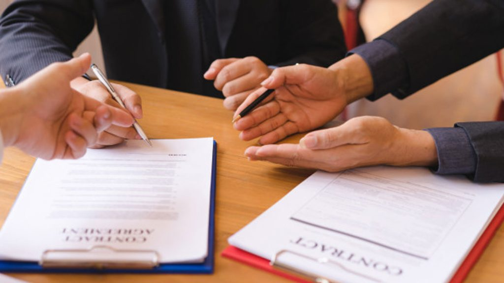 Close-up of three pairs of hands over two agreement contracts on an office table in Singapore