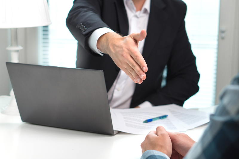 Licensed moneylender in black suit and white shirt extends hand to loan applicant in Singapore