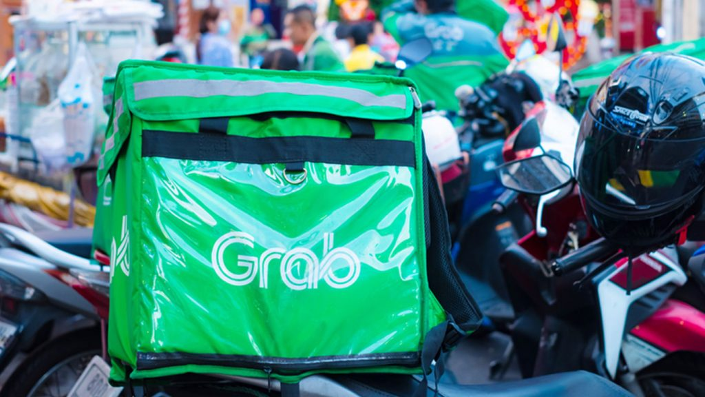 Green Grab delivery bag and black helmet on a parked motorcycle in Singapore