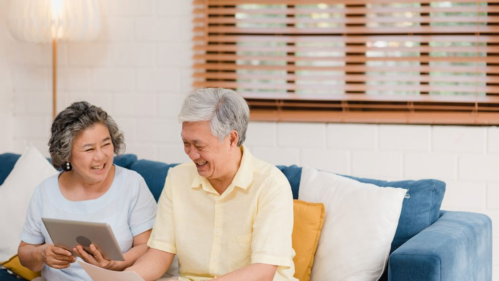 A retired couple with grey hair on a sofa look at a tablet in Singapore