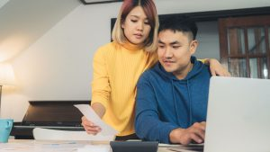 Standing woman in yellow turtleneck shows note to a seated man on laptop in Singapore