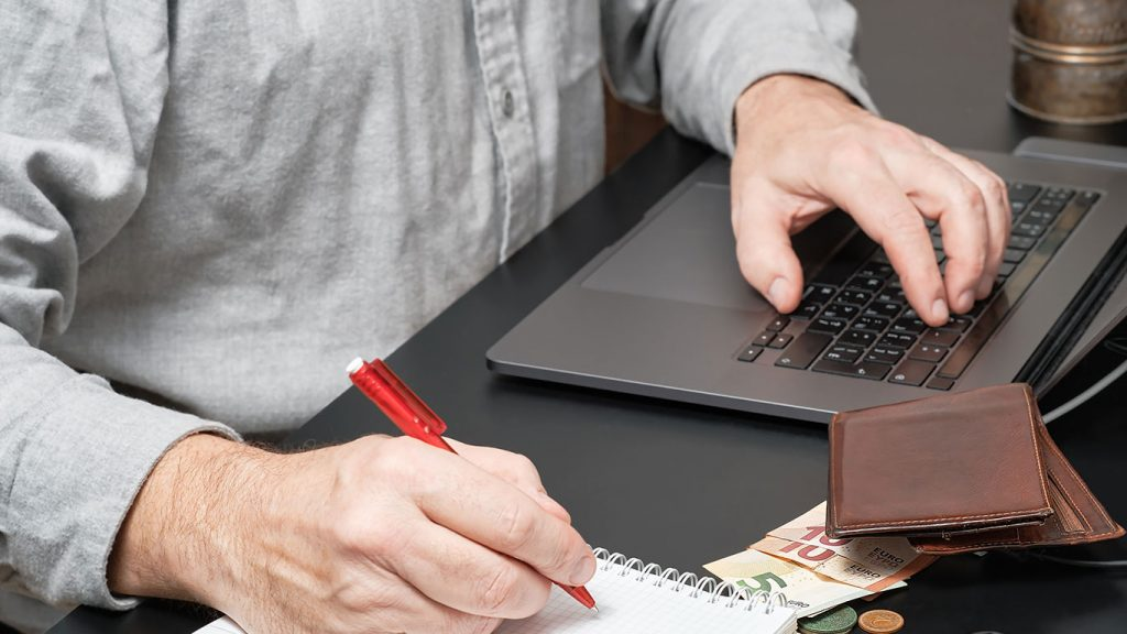 Wallet, cash and coins on a table as man works on a laptop in Singapore
